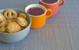 Tea and cookies. Cups of fruit tea and cookies on a woven mat (shellow DOF, focus on cookies Stock Photos