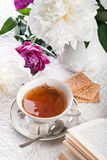 Tea with cookies, the book and flowers Royalty Free Stock Image