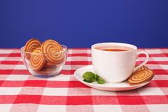 Tea and cookies. Cup of tea with lemon, mint and glass bowl of cookies, lying on checkered tablecloth, on blue background Stock Photography