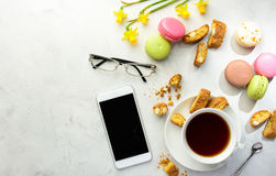 Tea with cookies, macaroons and smartphone with glasses Stock Photo