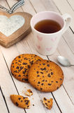 Tea, cookies and wooden heart. Composition on a light wooden background Stock Photos