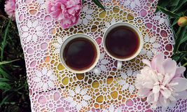 Tea in country style in summer garden. Two cups of black tea on handmade crocheted vintage lacy tablecloth and blooming peony. Tea in country style in summer royalty free stock photos