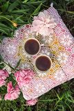 Tea in country style in summer garden. Two cups of black tea on handmade crocheted vintage lacy tablecloth and blooming peony. Tea in country style in summer stock photo