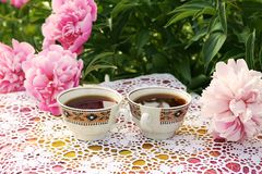 Tea in country style in summer garden. Two cups of black tea on handmade crocheted vintage lacy tablecloth and blooming peony stock photography
