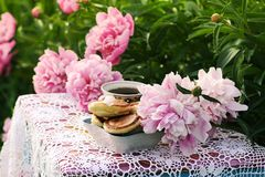 Tea in country style in summer garden. Two cups of black tea and pancakes on handmade crocheted vintage lacy tablecloth and. Tea in country style in summer royalty free stock photo