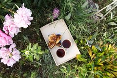 Tea in country style in summer garden in the village. Two cups of black tea and pancakes on wooden tray and blooming peony flowers stock photography