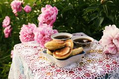 Tea in country style in summer garden. Two cups of black tea and pancakes on handmade crocheted vintage lacy tablecloth and stock photo