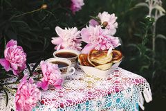 Tea in country style in summer garden. Two cups of black tea and pancakes on handmade crocheted vintage lacy tablecloth and. Tea in country style in summer stock image