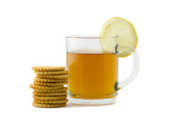 Tea and crackers. A cup of hot tea with a slice of lemon and crackers over white background Royalty Free Stock Photography