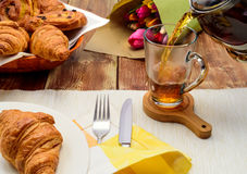 Tea with croissants, tea in a glass cup,. Croissant, tulips, bake, pouring royalty free stock images