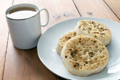 Tea and Crumpets on Wooden Table. Tea and crumpets on a rustic wooden table Royalty Free Stock Photos