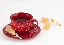 Tea and crystal sugar. Black tea in a red mug, stick with crystal sugar Stock Photo