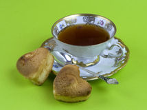 Tea,Cup. A cup of tea and biscuits on a green background royalty free stock image