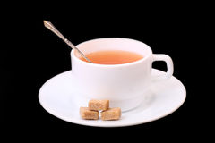 Tea cup. A cup of tea with chunks of brown sugar in a cup. Black background Stock Photo