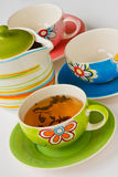 Tea cup. Colorful ceramic cup with tea and teapot Royalty Free Stock Photos
