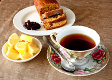 Tea cup. An arrangement of a tea cup, dish of diced lemons and sliced bread and jam Stock Images