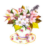 Tea cup with autumn leaves, cherry flowers and vintage feathers. Stock Image