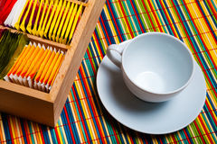 Tea cup and bags. An empty cup and a wooden box with inside some bags of tea. Background colorful to strips of wood. High definition royalty free stock photos