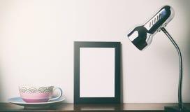 Tea cup and blank photo frame light on a shelf. Tea cup and blank photo frame light up on a shelf Stock Photos