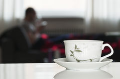 Tea cup with blurred person in background Royalty Free Stock Images