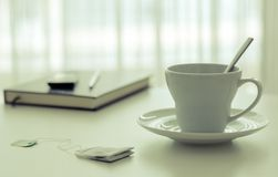 Tea cup beside a book and pen near the window. royalty free stock photo