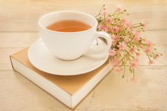 Tea cup on book, vintage style light Royalty Free Stock Images