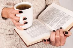 Tea cup and book in young women hands with black nails and sweater. Young Girl hand with black nails manicure holds book and tea cup, woman in wool sweater Stock Photography
