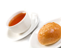 Tea cup and bun against Stock Images