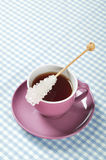 Tea in cup with candy sugar. On checkered background Royalty Free Stock Photos