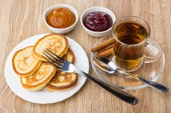 Tea in cup, cinnamon, pancakes, bowls with jam and fork Royalty Free Stock Image