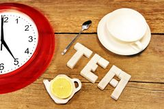 Tea cup, clock and sign made from sugar on brown wooden table Royalty Free Stock Photos