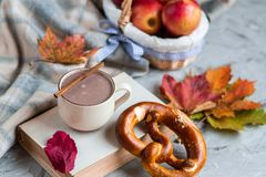 Tea Cup with Coffee Hot Chocolate Autumn Time Bakery Pretzel Toned Photo Knitting Scarf Blanket. Yellow Leaves Gray Background royalty free stock photography