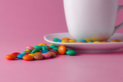 Tea cup with colored sweet dragees on saucer. Closeup view Stock Image