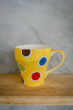 Tea cup and colourful dots on wooden shelf. Royalty Free Stock Photography