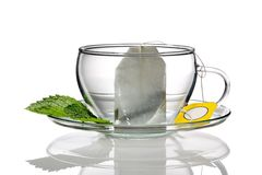 Tea cup concept. Empty tea cup with teabag, isolated on white background with reflection stock photo