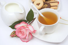 Tea cup with cookies, milk and a rose Stock Photos