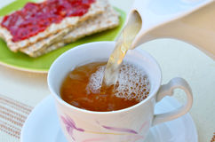 Tea in cup with crispy bread and jam Stock Photography