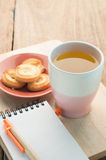 Tea cup, dessert cookie on wood floor and notepad paper. Royalty Free Stock Photography