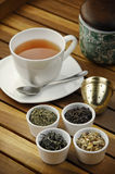 Tea. Cup of tea with different sorts of tea leaves in bowls Stock Image