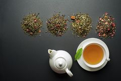 Tea in cup with dry tea collection. Cup of tea with dry tea collection of different types stock photos