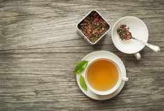 Tea in cup with dry tea collection. Cup of tea with dry green and herbs tea collection on wooden table stock photo