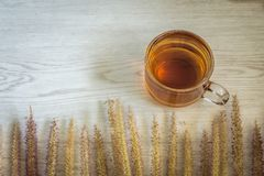 Tea cup and Flowers grass on white wooden background. Nature with vintage style, Morning with hot tea Royalty Free Stock Photography
