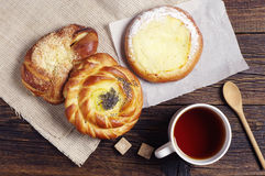 Tea cup and fresh buns Stock Images