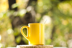 Tea cup in the garden. A yellow tea cup on a table in the garden royalty free stock photography