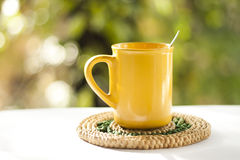 Tea cup in the garden. A yellow tea cup on a table in the garden royalty free stock images