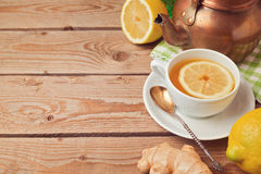 Tea cup with ginger and lemon on wooden table with copy space Royalty Free Stock Images