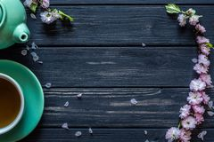 Tea, teapot and sakura on a black background. Tea in a cup, green kettle and sakura on a black wooden background Stock Images