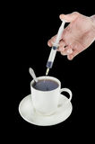Tea cup with a hand using a syringe Stock Photo