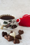 Tea cup with heart shaped chocolates. Red heart on gray wooden background. Valentine's day tea-time Royalty Free Stock Photos