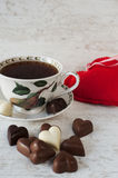 Tea cup with heart shaped chocolates. Red heart on gray wooden background. Valentine's day tea time still life Royalty Free Stock Images